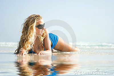 Girl on beach with reflection in water