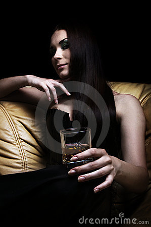 Young woman lying on sofa with a glass of whisky
