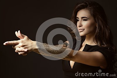Beautiful tattooed woman with luxuriant shining wavy hair and perfect make up pretending to aim something with shooting gesture