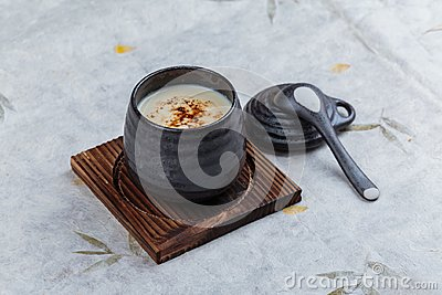 Japanese custard pudding torched caramel on top served in black ceramic cup on wooden plate with lid and spoon on washi.