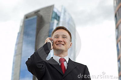 Happy young businessman talking on the phone