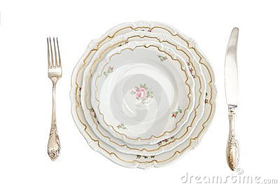 Dinner set with three plates, knife and fork isola
