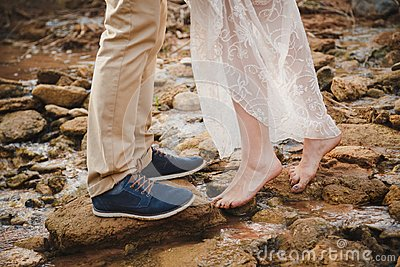 Outdoor wedding ceremony, close up of young woman feet standing barefoot on stones in front of mans feet wearing dark blue shoes
