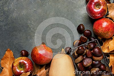 Ripe Organic Red Glossy Apples Pomegranates Chestnuts in Wicker Basket Dry Autumn Leaves Scattered on Dark Stone Background.