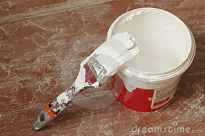 Brush soaked in white paint and pot
