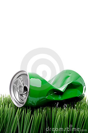 A green crushed aluminum drink can on grass