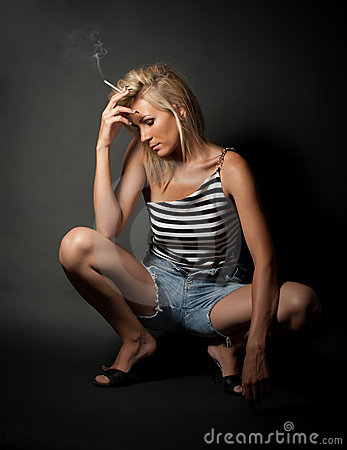 Blond girl in stripped shirt smoking cigarette