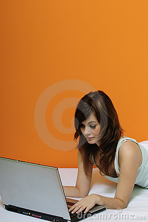Cute brunette girl using laptop in bed
