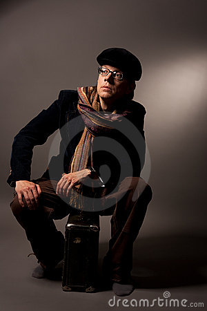 Man in glasses sitting on suitcase