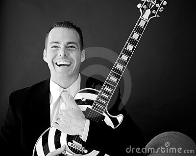 Groom Holds His Guitar and Laughs