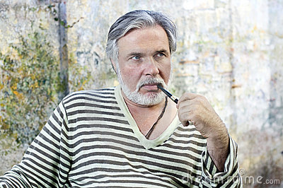 Mature man smoking tobacco pipe