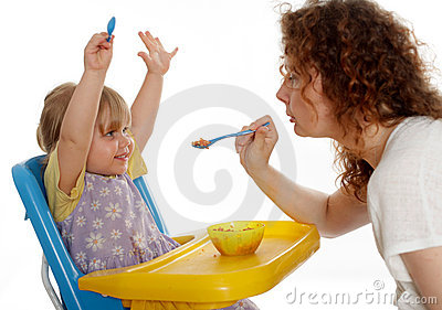 Young woman feeding little girl