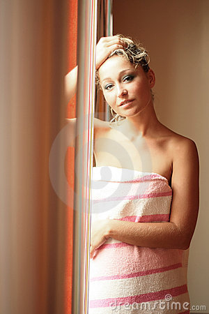 Young blonde stands beside a window