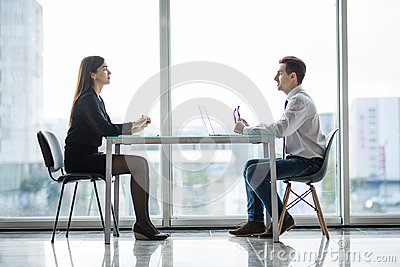 Businessman and woman having a discussion in the office face to face at table against windows