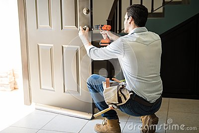 Young man fixing a door lock