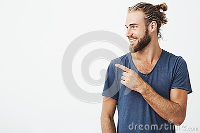 Profile of cheerful handsome man with fashionable hairstyle and beard smiling brightfully and pointing at free space for