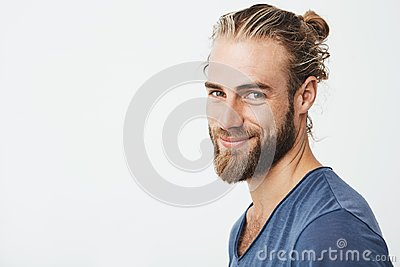 Close up portrait of handsome manly guy with beard posing in three quarters, looking in camera and happily smiling