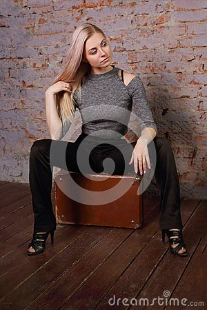 Beautiful young woman posing near brick wall