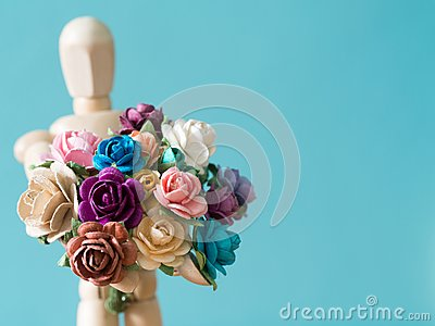 Select focus of flower. The wooden puppet holds flower and standing on the wood table. the background is blue and copy space