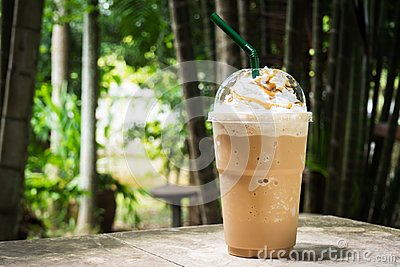 Coffee blend in plastic cup. Served with whipped cream topping and sweet syrup.