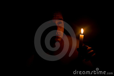 Man holding candle in dark