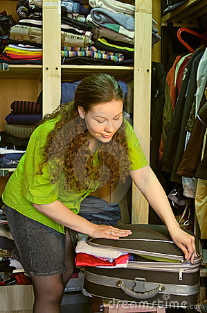 Housewife in the wardrobe packs a suitcase