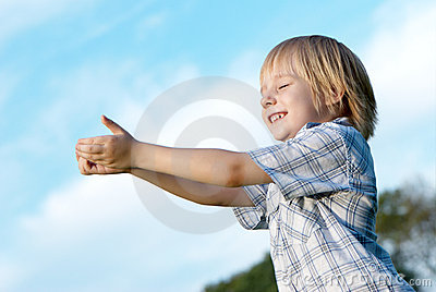 Little boy with stretched hands to sky