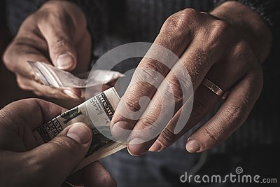 Hand of addict man with money buying dose of cocaine or heroine or another narcotic from drug dealer. Drug abuse and traffic