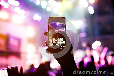 Music fans takes picture of stage in concert on smartphone.