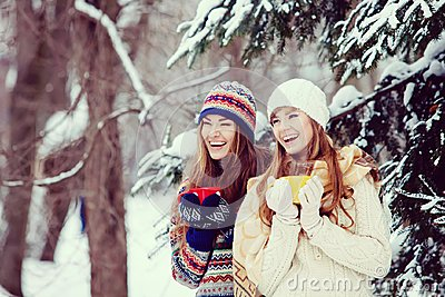 Two young women with colorful cups drinking tea outdoor and smil