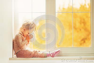 Little cute Kid Girl sitting by window indoor holding cup of hot drink cocoa enjoying autumn forest background. Season Beauty