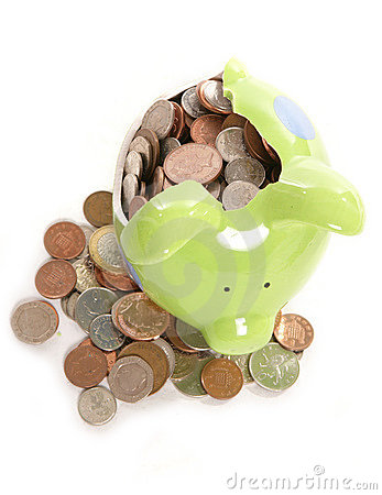 Smashed piggy bank with British currency coins