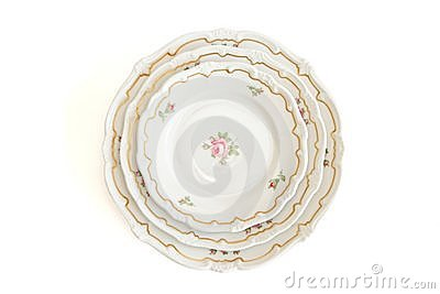 Stack of three white plates and saucers top view