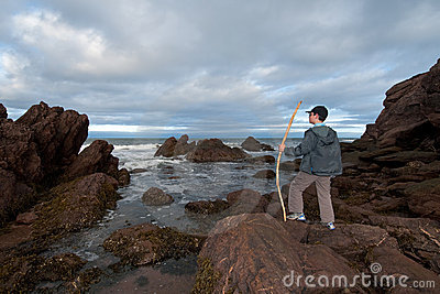 Boy views Sea and Rocks