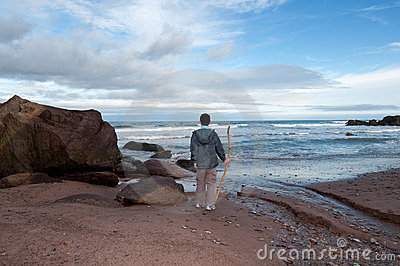 Young boy on a rocky beach stares out to sea