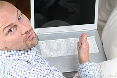 Man with Laptop sitting on Sofa