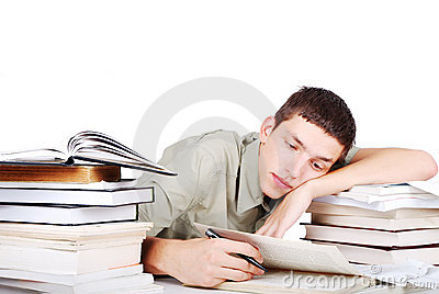 Young man with many books siting and writing