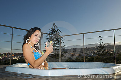 Woman having relax in jacuzzi under blue sky