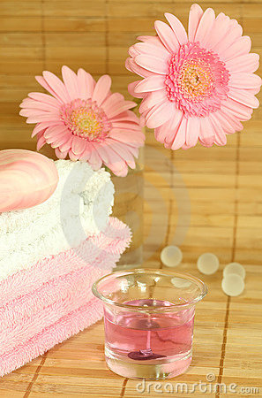 Towels, soap, candle and flowers.
