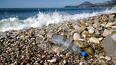 The waves of the sea washed up an empty plastic bottle. Environmental pollution - garbage in scenic spots