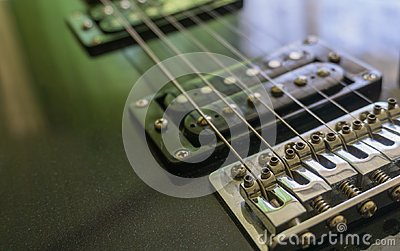 Electric guitar part close-up. Neck and humbucker pickup. Horizontal composition. Studio shot.