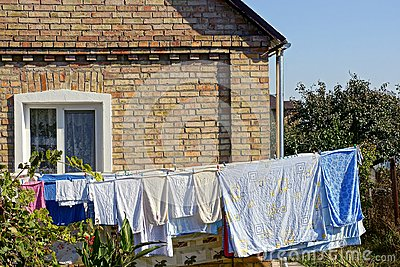 Clothing and linen dries after washing in the yard near the wall of the house