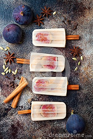 Masala chai latte popsicles with figs on cinnamon sticks. Spiced ice lollies for fall, winter season. Christmas holiday dessert
