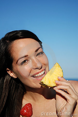 Attractive woman eating fruit