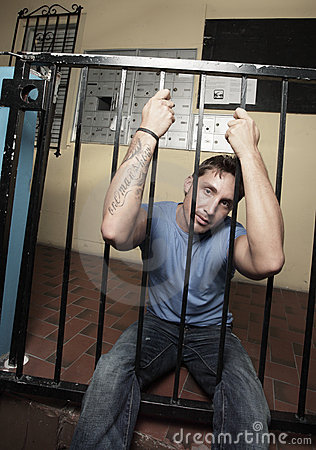 Man sitting behind bars
