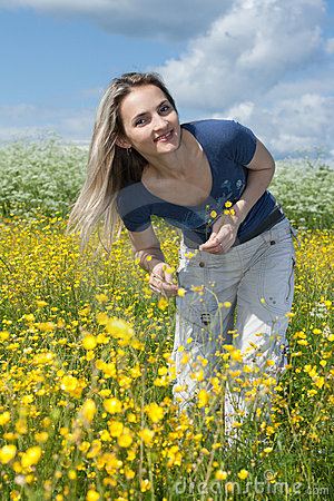 Beautiful girl in field with yellow flower