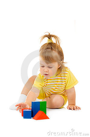 Small girl in yellow build toy pyramid