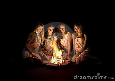 Teenage girls around campfire
