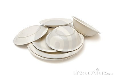 Pile of beige dinner plates, soup plates and sauce