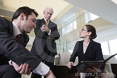 Business team in lobby meeting to review papers